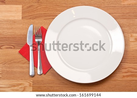 Ceramic white plate with knife and fork on wooden background  - stock photo