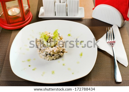 ceramic white plate with salad , on table in restaurant