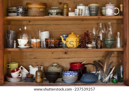 ceramics and kitchen equipment on rustic and country style wooden shelves