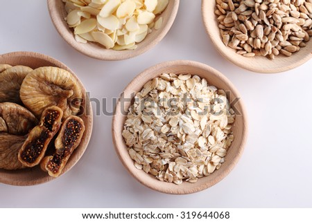 cereal and grain in wooden bowl- oat, fig, sunflower seed and almond - top view - stock photo