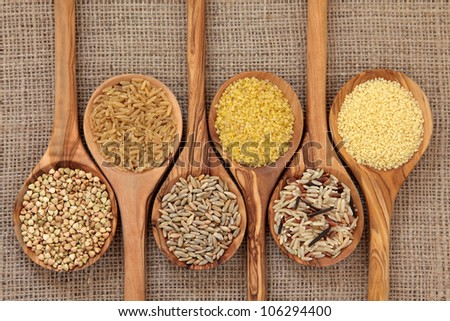 Cereal and grain selection of bulgur wheat, buckwheat, couscous, rye grain and brown and wild rice in olive wood spoons on hessian sacking background. - stock photo