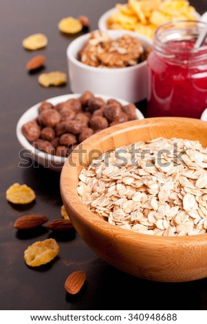 cereal and various delicious ingredients for breakfast on black table, close up