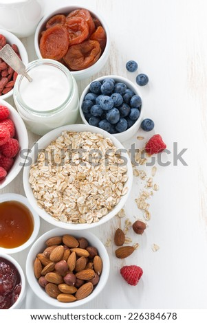 cereal and various delicious ingredients for breakfast on white wooden table, top view, vertical - stock photo