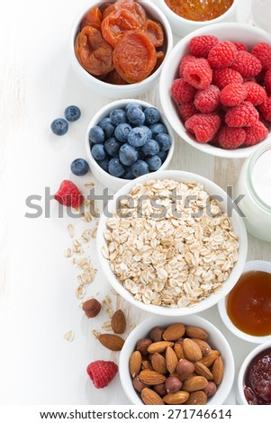 cereal and various delicious ingredients for breakfast, top view, vertical - stock photo