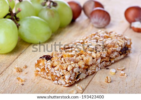 Cereal bar with grapes and hazelnuts on wood - stock photo