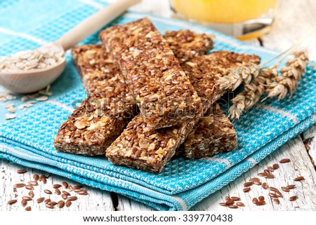 cereal bars, oatmeal, flax seeds and orange juice on a wooden background - stock photo