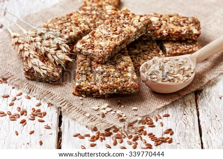 cereal bars, oatmeal, flax seeds on a wooden background - stock photo