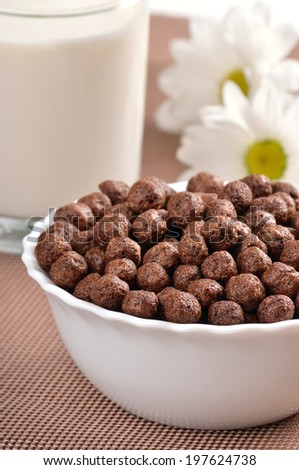 Cereal chocolate balls in bowl and glass of milk - stock photo