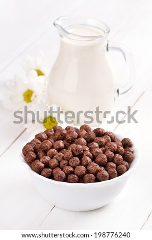 Cereal chocolate balls in bowl and jug of milk - stock photo