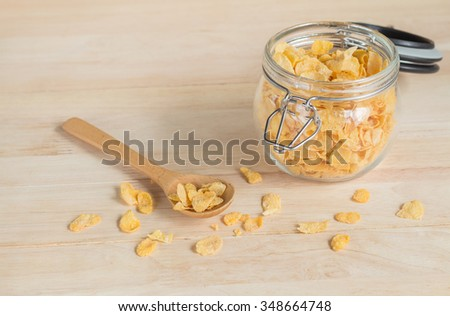 cereal cornflakes in the glass jar and spilling out to the wood table - stock photo