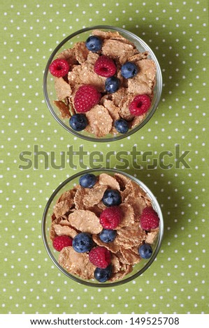 cereal flakes with raspberry and blueberry in glass bowl - stock photo