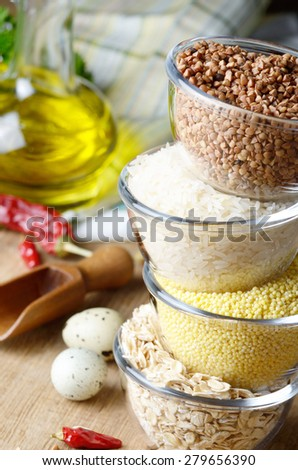Cereal grains set in glass bowls on wooden table - stock photo
