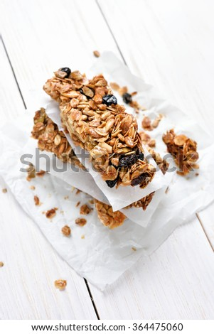 Cereal granola bars stacked on baking paper over white wooden table, top view - stock photo