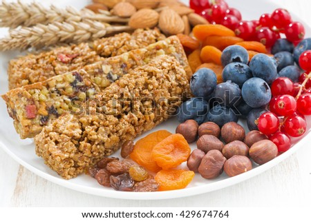 cereal muesli bars, fresh and dried fruit on a plate, closeup, horizontal - stock photo
