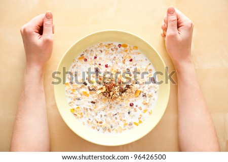 Cereal muesli breakfast with dried fruit and nuts and milk and woman hands on table. Top View