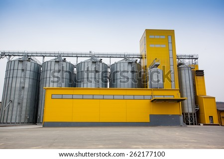 Cereal silos with a yellow building - stock photo