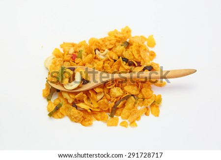 cereal with cashew nut and kiwi in a wooden spoon against pile of cereal with cashew nut and kiwi on white background