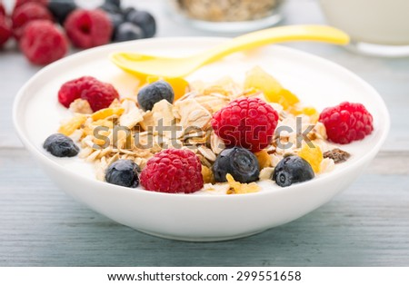 Cereals and cornflakes with raisins and fresh berries.