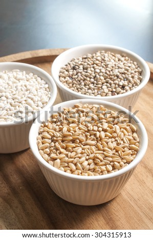 Cereals and grains in ceramic cup on a wooden plate.