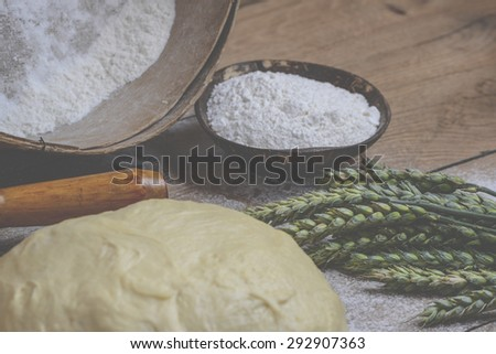 Cereals, flour and dough on wooden background