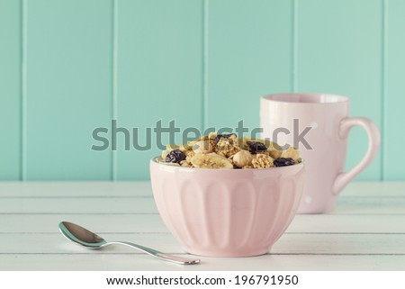 Cereals in a pink bowl on a white wooden table with a robin egg blue background. Vintage style. - stock photo
