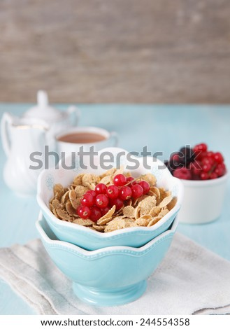 Cereals in the blue bowl with milk, coffee and fruit on the back, selective focus - stock photo