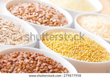 Cereals in white bowls: oats, millet, rice, buckwheat, wheat, spelt - stock photo