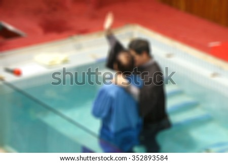 Ceremony of baptism blurred background. person christ babies priest baptism religion mature emotions child candle water indoors christianity events new Birth victory death New life pond dip Dead toSin - stock photo