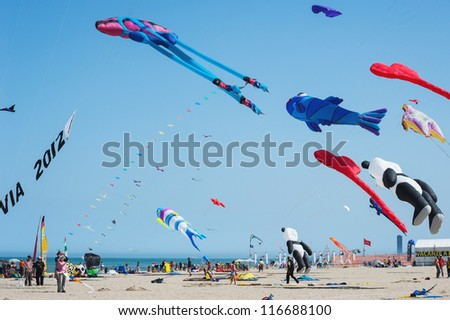 CERVIA, ITALY - APRIL 27: Sky full of kites for International Kite Festival on April 27, 2012 in Cervia, Italy. This Festival brings together kite flyers from all over the world every year since 1981. - stock photo