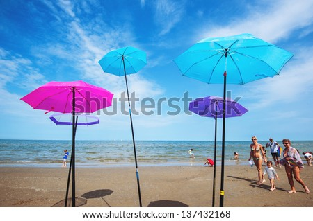 CERVIA, ITALY - APRIL 25: Umbrellas on the beach for International Kite Festival on April 25, 2013 in Cervia. This Festival brings together kite flyers from all over the world every year since 1981. - stock photo