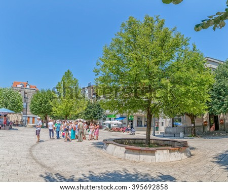 CETINJE, MONTENEGRO - AUGUST 11, 2015: Tourists and locals passing by in a leisurely stroll on the Dvorski Square.