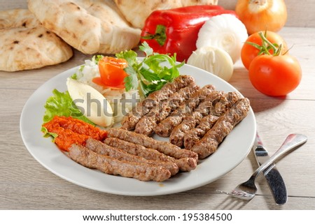 Cevapcici, a small skinless sausage cooked on the barbecue and served with: Lepinja bread, pickled red capsicum and Kajmak cheese. This dish is popular all over the Balkans - stock photo