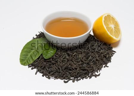 Ceylon black tea brewed into a bowl, dry tea leaves and lemon.