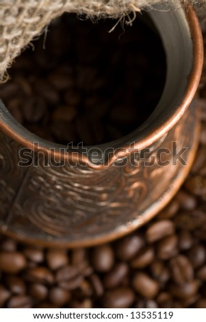 Cezve with freshly roasted coffee beans on sackcloth. Shallow depth of field. Focus on cezve throat