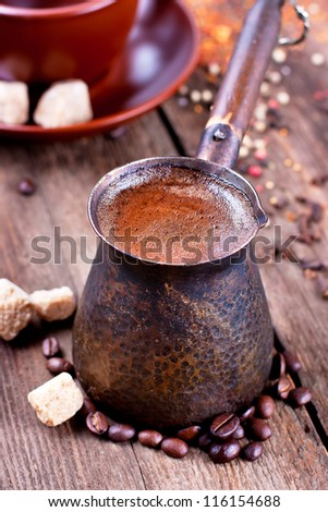 Cezve with hot coffee on a wooden surface - stock photo