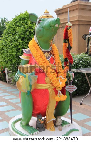 Chachoengsao, Thailand - May 4, 2015: Mouse is Lord Ganesha's Mount. Wishing that their wishes will be conveyed to the God, people whisper into mouse's ears while placing a hand over the other ear. - stock photo