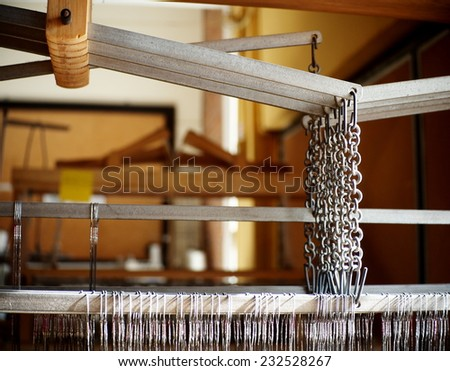 chain and levers, close-up parts of a manual small weaving machine for making education arts and crafts textiles with light and shadow in a university's fashion and textiles workshop in THAILAND