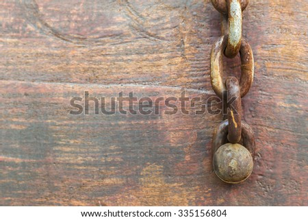 Chain are fastened with pin on old wood. - stock photo