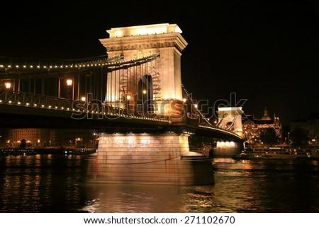 Chain bridge with tall pillars illuminated by night, Budapest, Hungary - stock photo