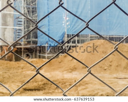 Chain link fence shot close up,Construction Building and sand in the background.