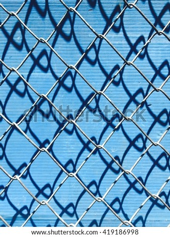 Chain Link Fence with shadow on blue background. - stock photo
