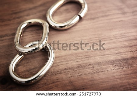 Chain links or chrome metal links on a grungy wooden table. shallow depth of field.