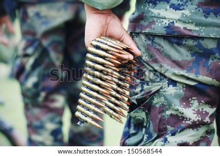 chain of 7.2 mm bullet on hand - stock photo