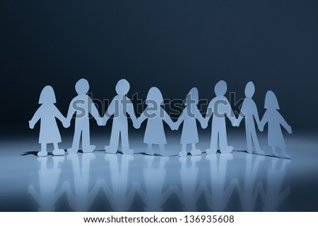 Chain of paper cut people in spotlight against a dark background - stock photo