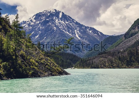 Chain of rocky peaks, azure lake and crooked tree on the shore