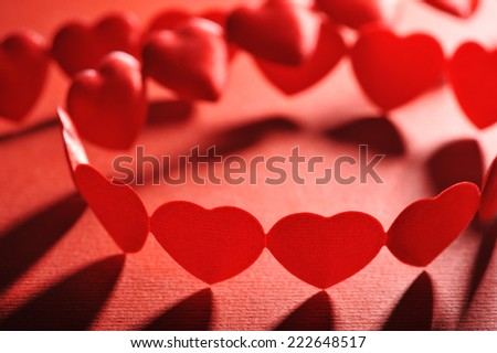chain of small red textilehearts on red background