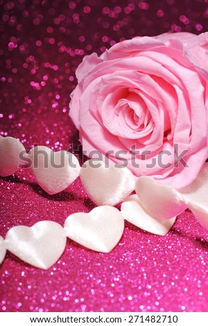 chain of white textilehearts with pink rose on pink sparkle background - stock photo