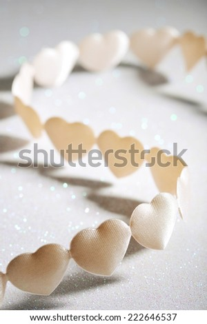 chain of white-yellow textilehearts on silver sparkle background