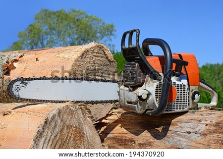 Chain saw on logs - stock photo