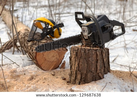 Chain saw on pine stump and protective visor with hearing protection on the fallen tree in winter - stock photo